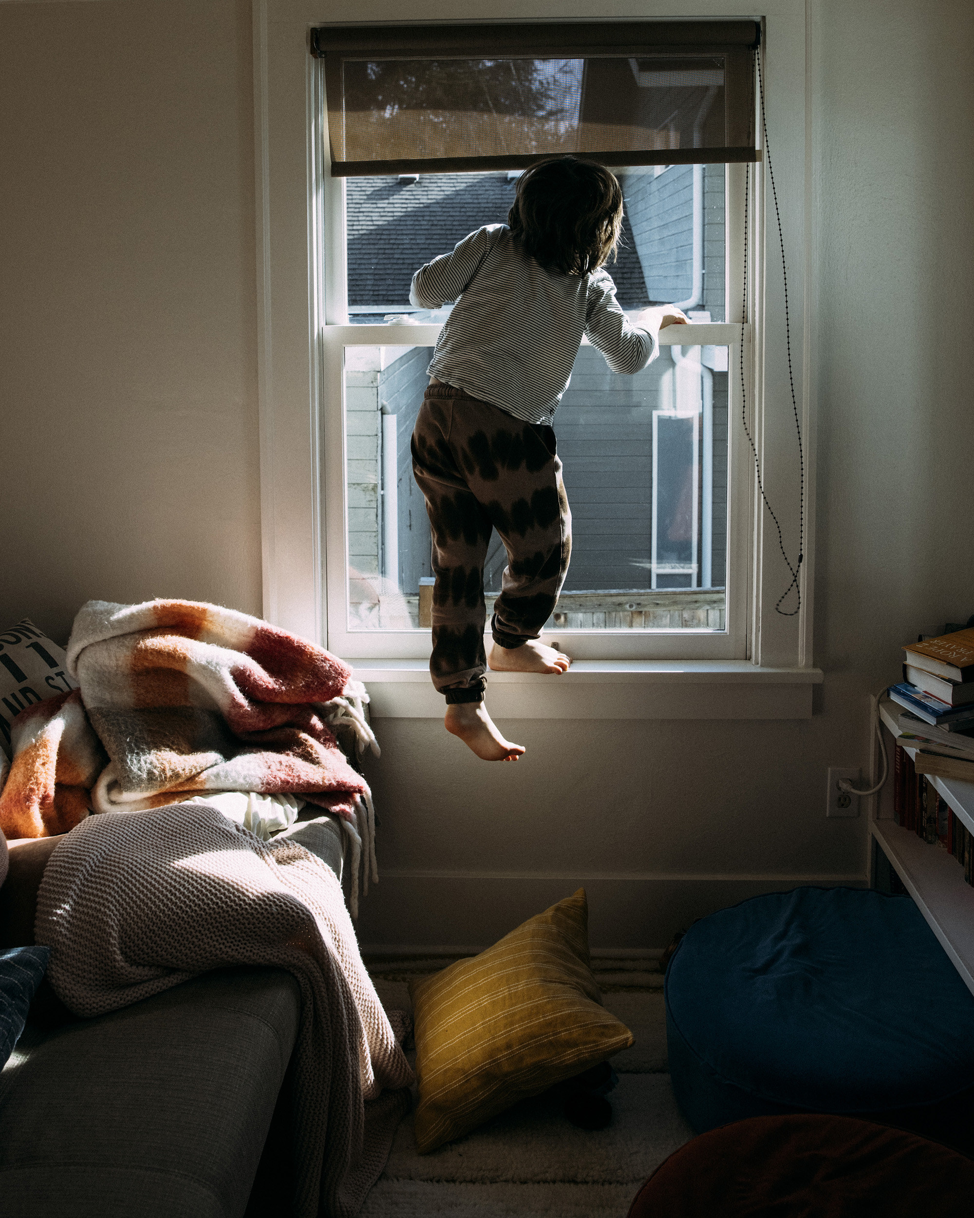 A toddler stands on a window ledge with pillows and books strewn about the floor