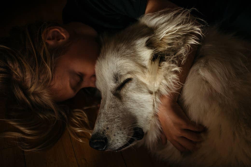 A sleeping girl hugs a dog