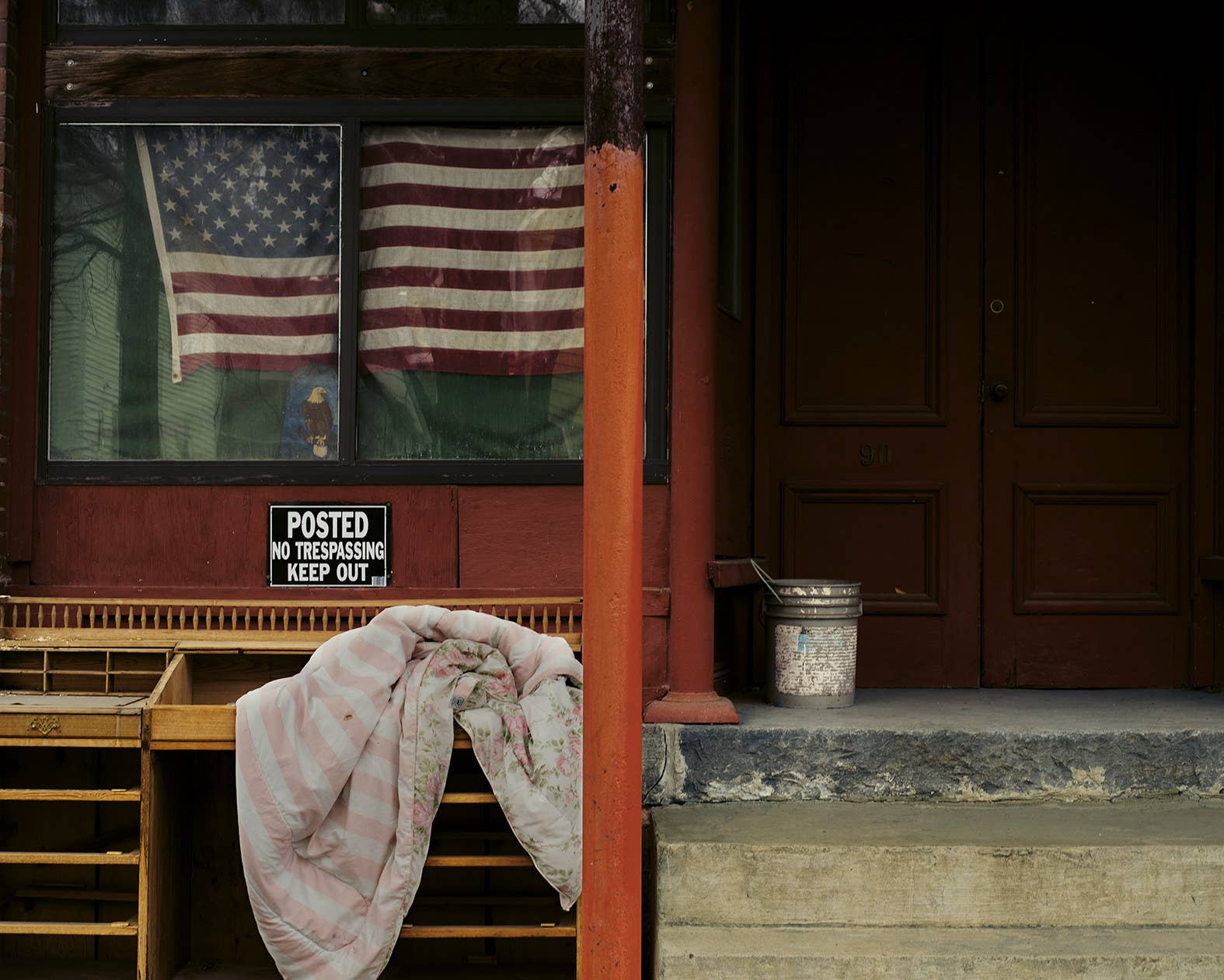 "An American flag in the window of a store with a sign that says ""no trespassing"""
