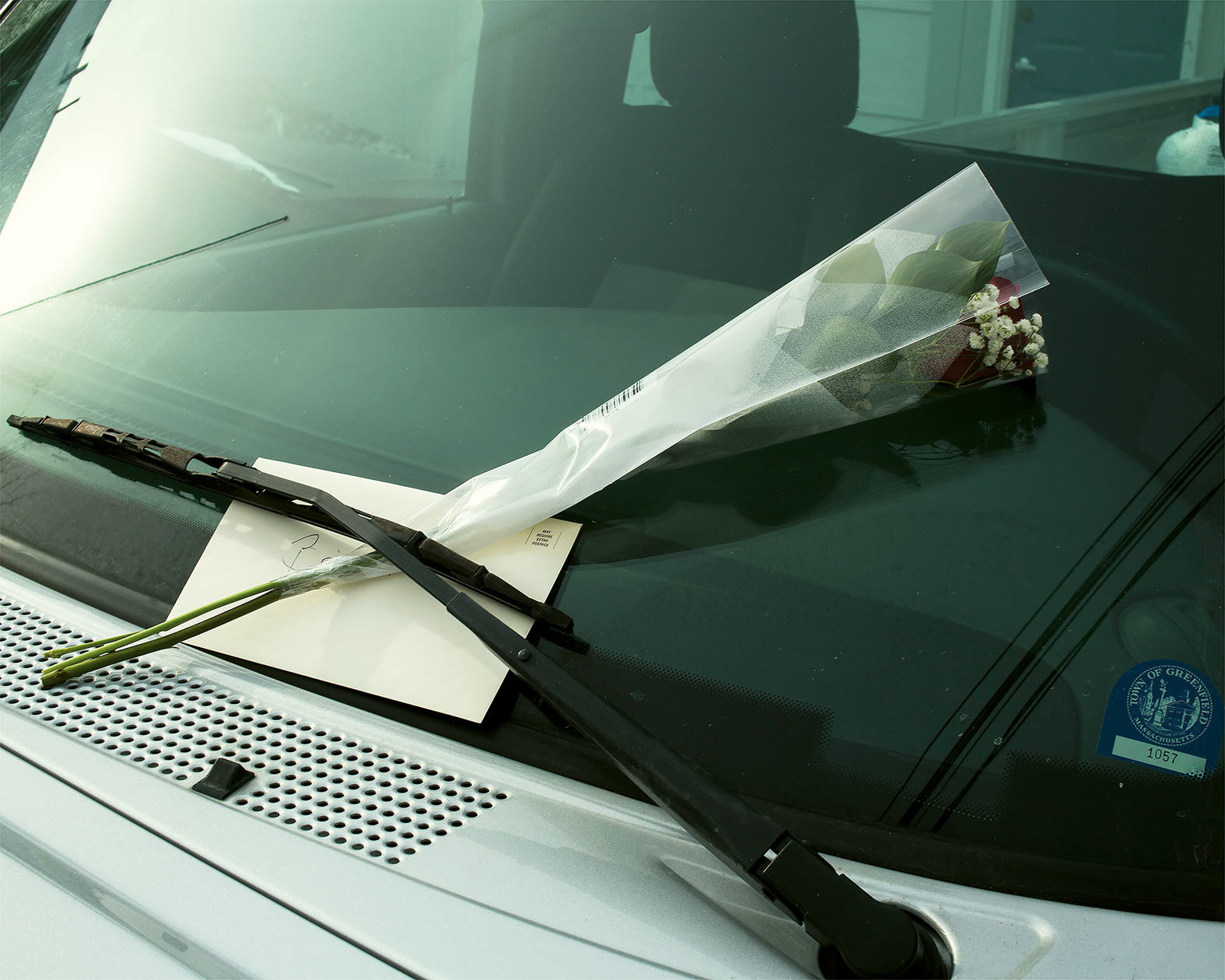 A flower and a card on the windshield of a car