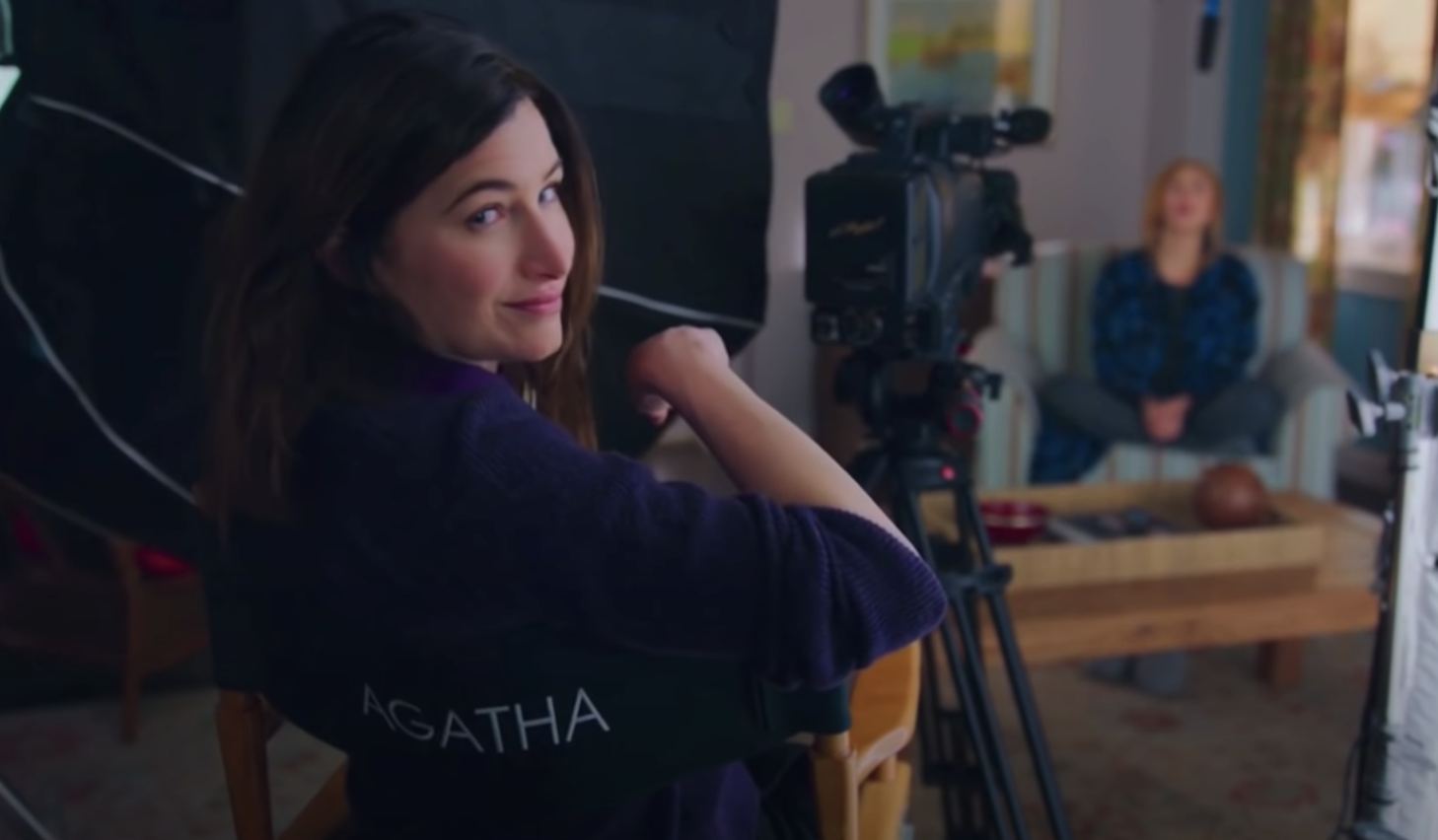 "Agatha sitting in a director's chair while filming the ""Modern Family""-esque episode for ""WandaVision"""