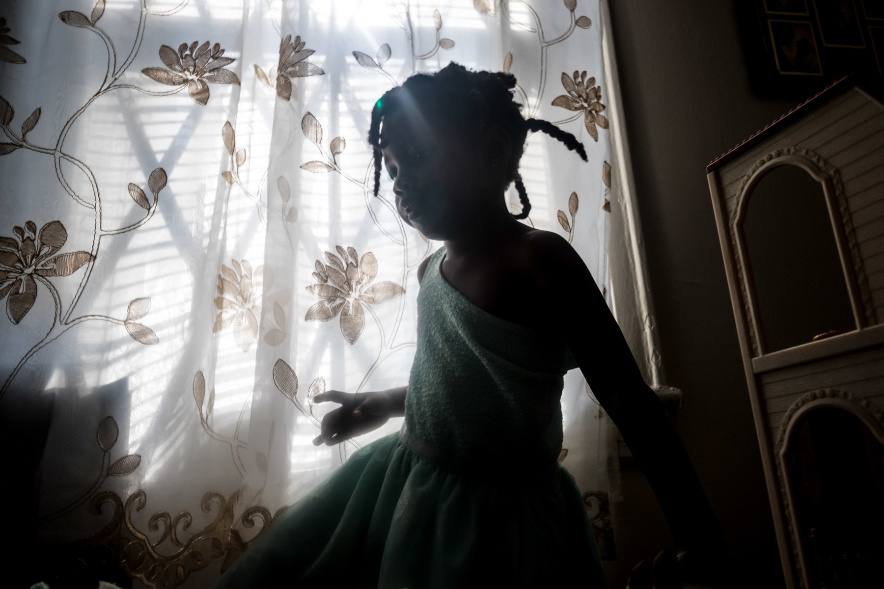 A toddler in a dark room stands by a window curtain with flowers embroidered on it
