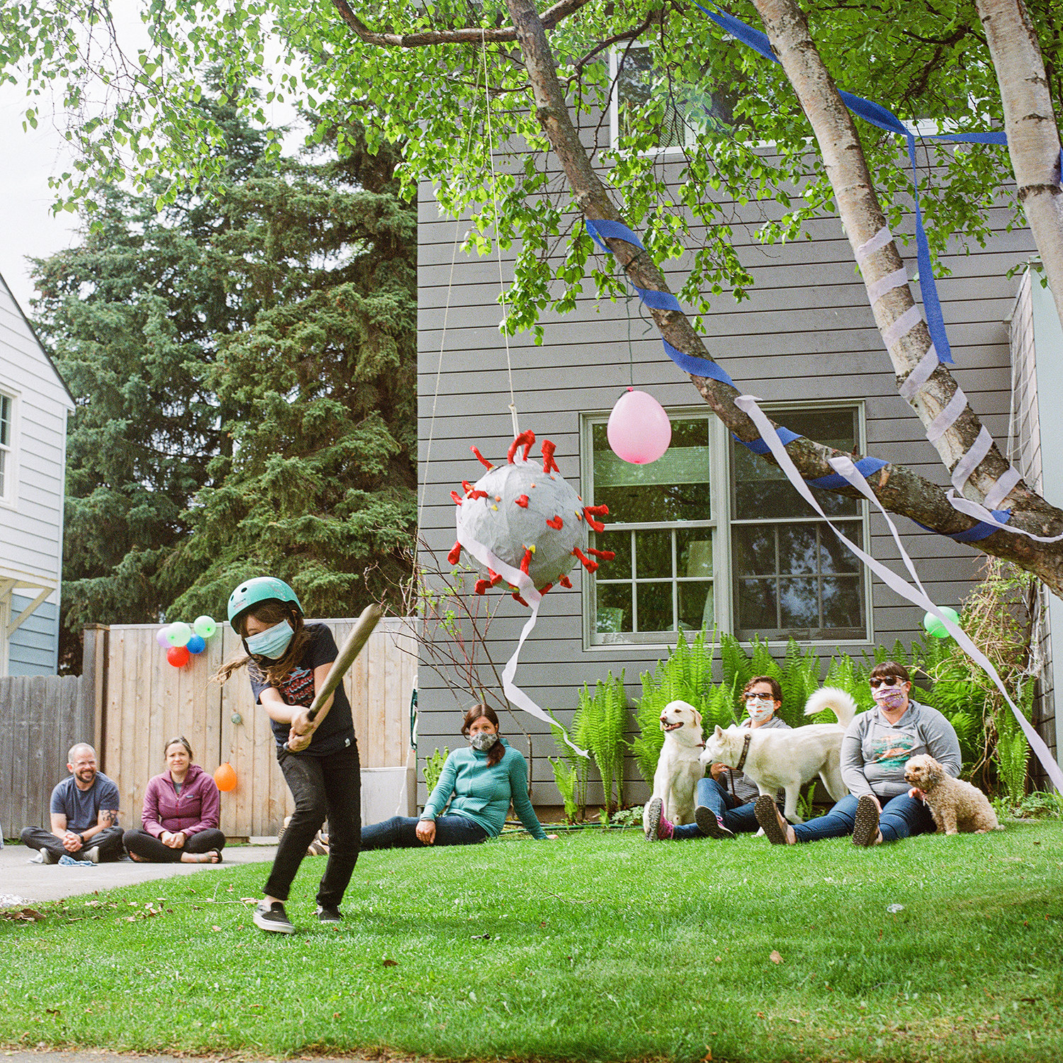 A group of adults watch a kid hit a piñata resembling a coronavirus particle with a bat in a neighborhood front yard