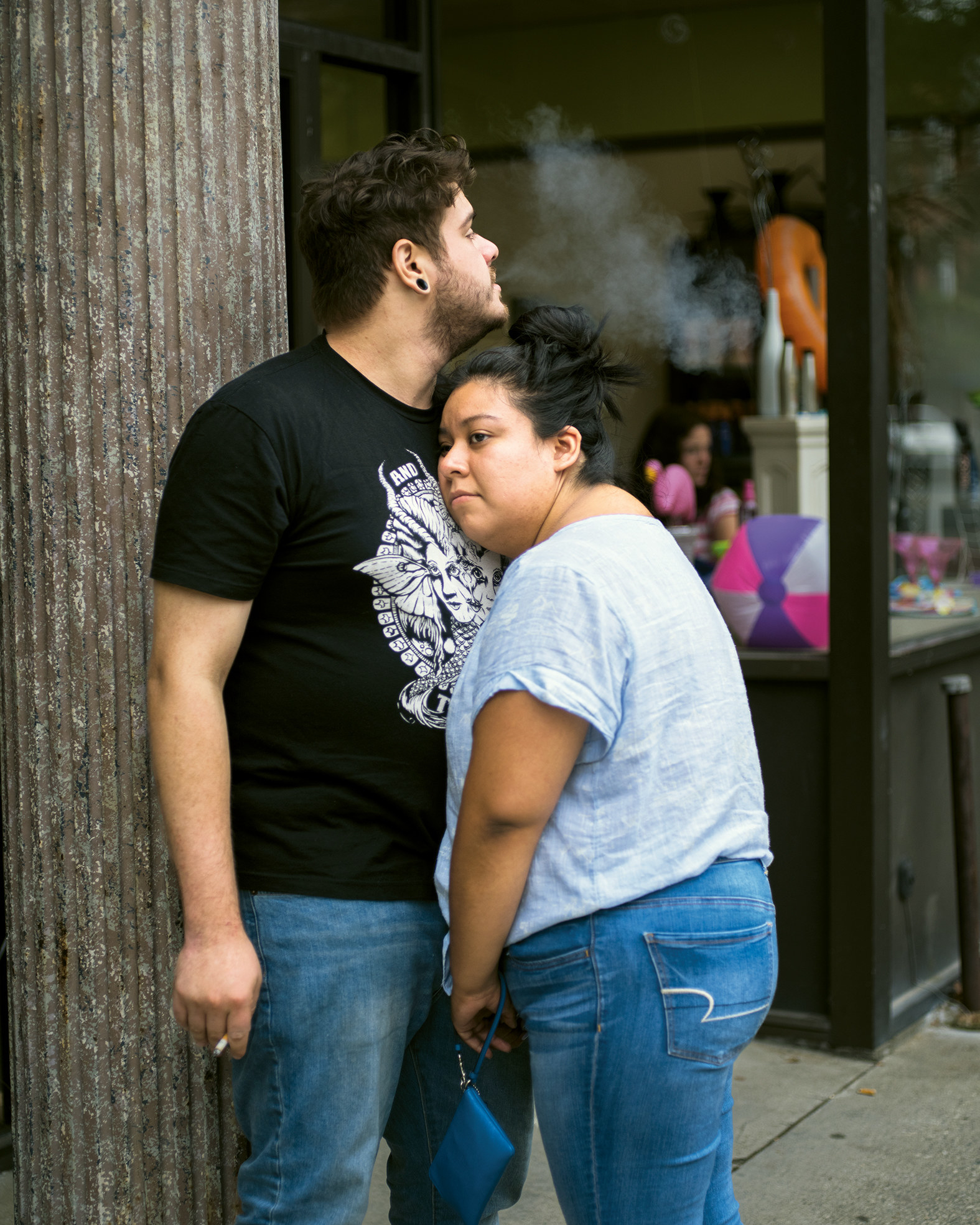 Two people embrace while smoking cigarettes