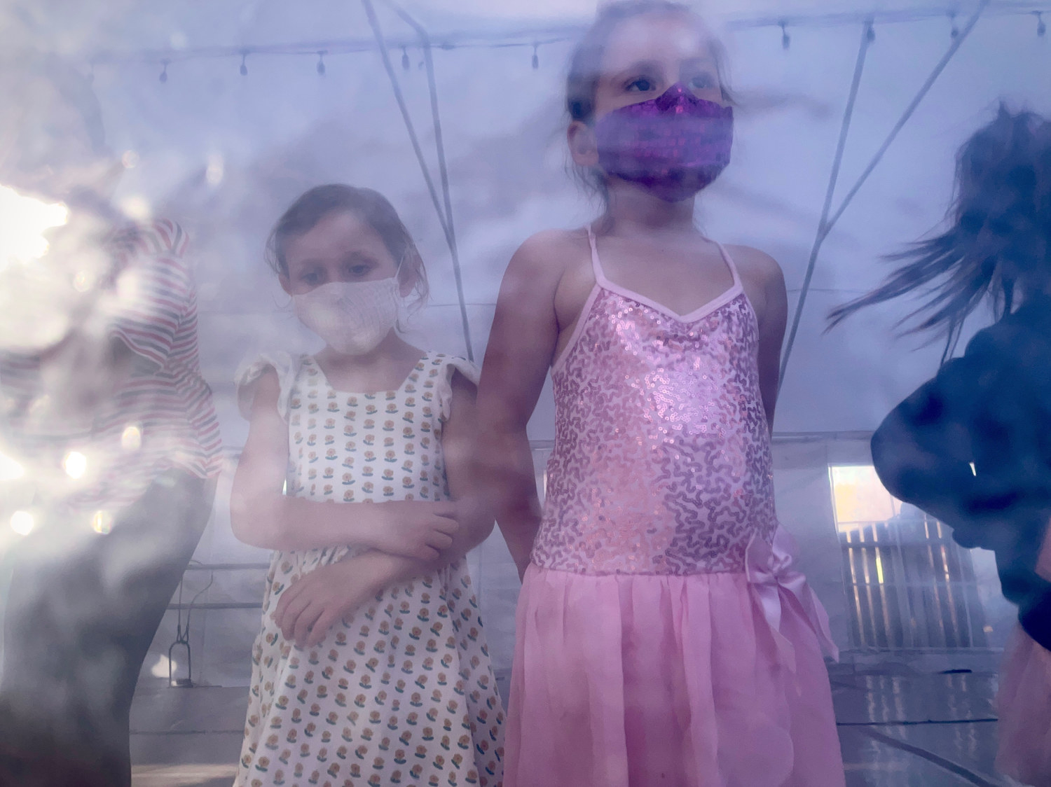 Two girls in dance gear and face masks look out from the inside of a tent