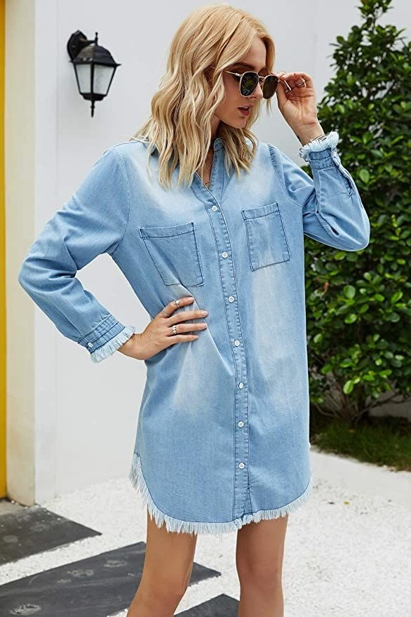 A model wearing the long-sleeved mini dress with frayed cuffs in light wash denim