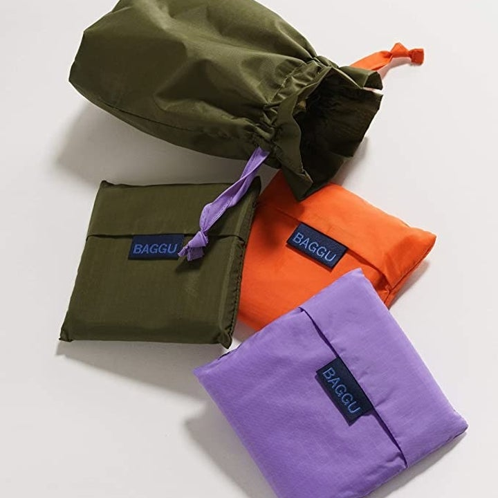 The three bags folded up into three corresponding pouches next to a larger drawstring pouch they all will fit into