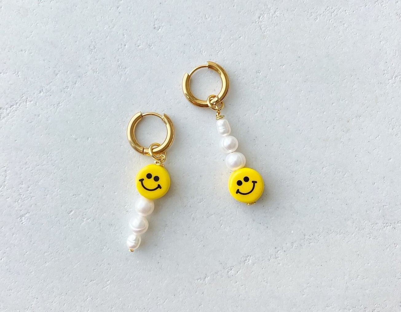 gold hoop earrings with pearls hanging from them and a smiley face on each one