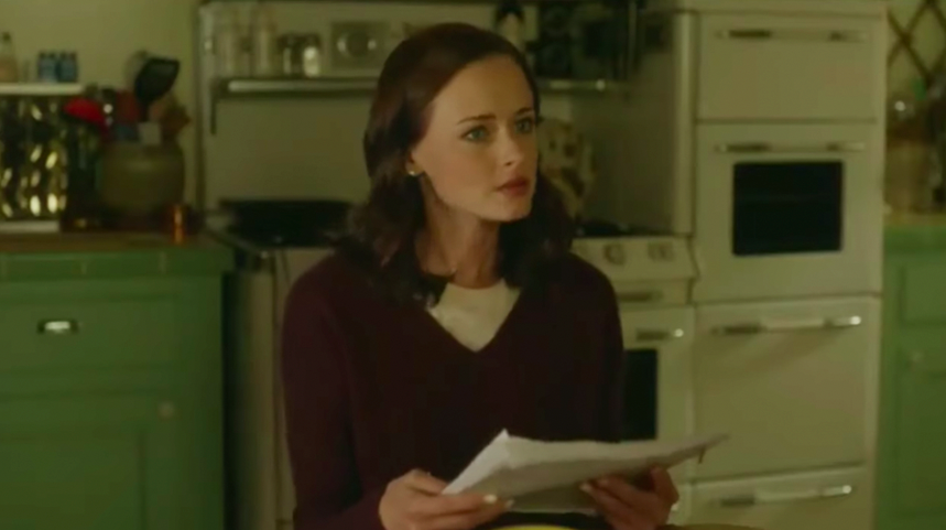 """Rory Gilmore in """"Gilmore Girls: A Year in the Life"""" holding a transcript of her book"""