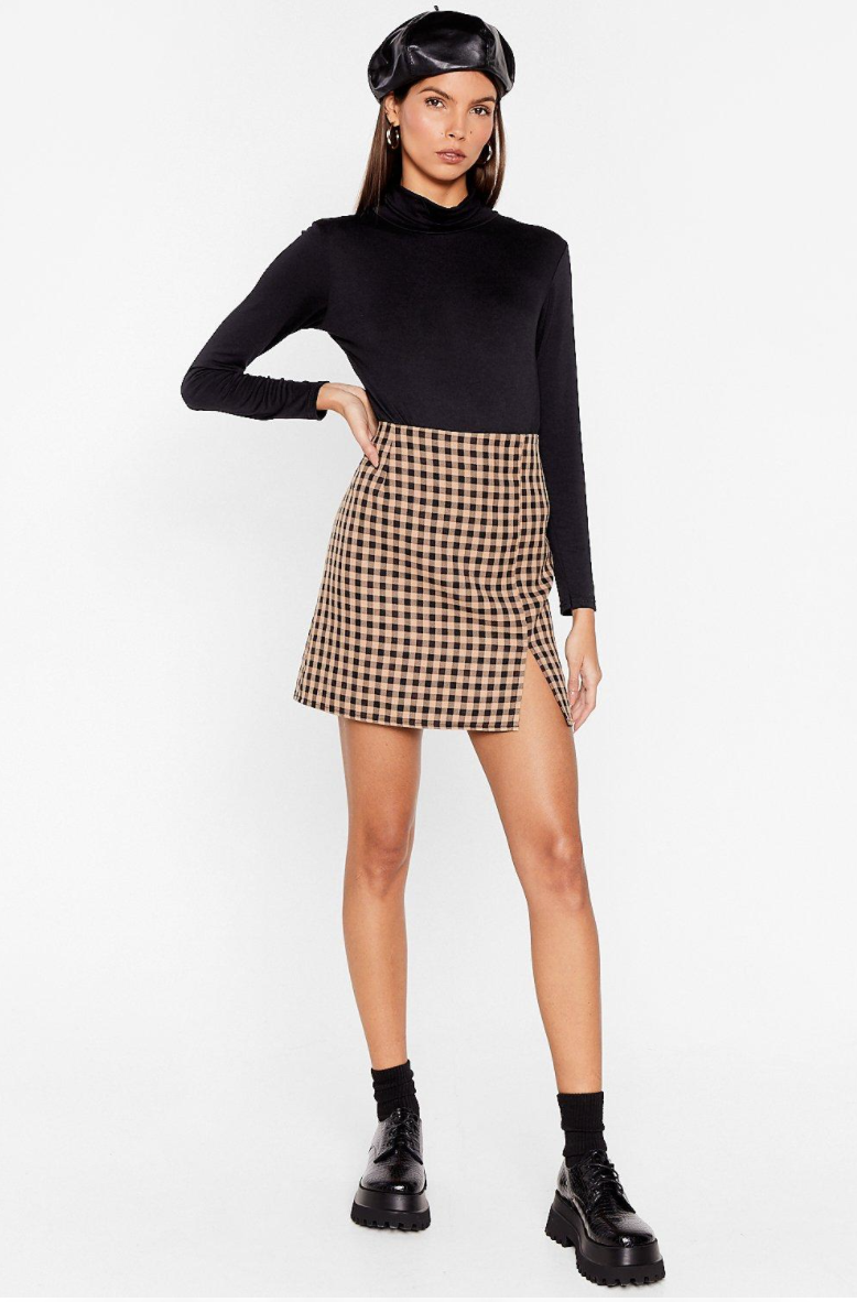 person wearing the bodysuit with a skirt and black boots