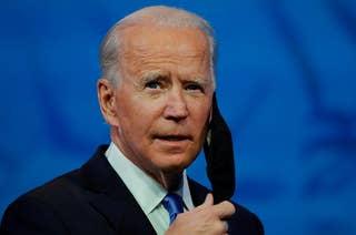 President Joe Biden taking off his face mask before giving a speech