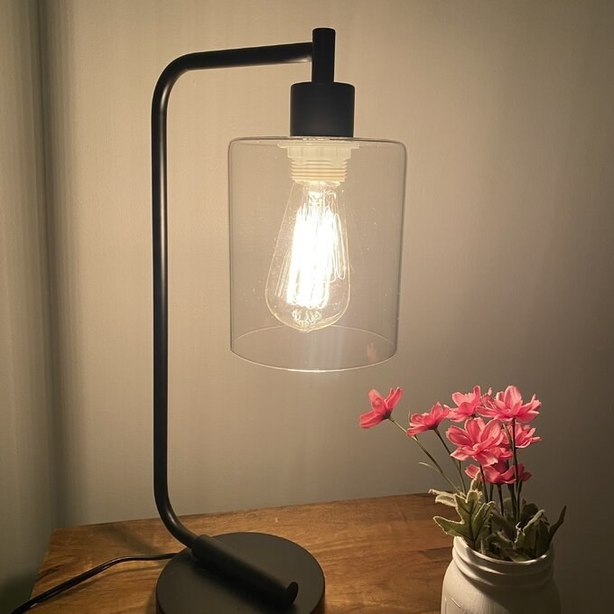 Desk lamp in a black finish with an Edison bulb and glass lamp shade