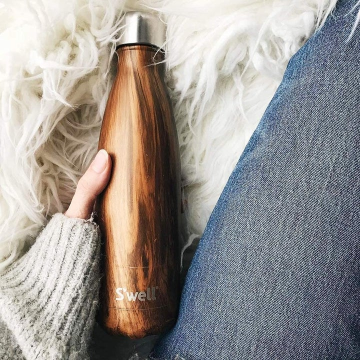 A hand holding a S'well water bottle with a teakwood finish