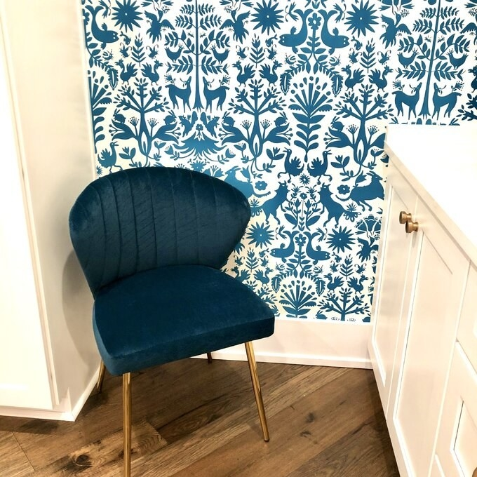 a blue velvet tuft chair with gold legs in a room