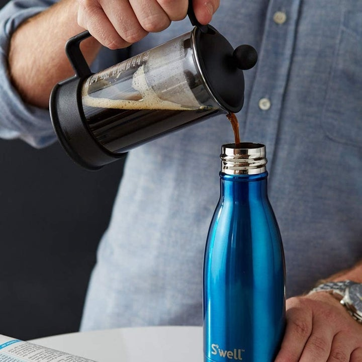 A model pouring coffee into a blue water bottle