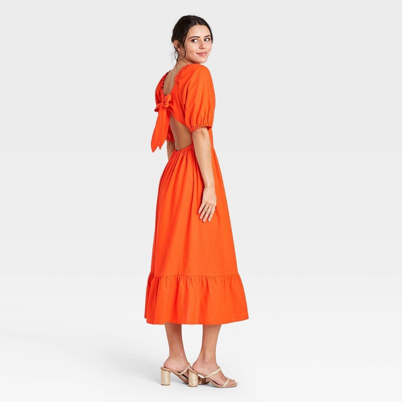 Orange midi dress with ruffle hem skirt, goes past the ankle