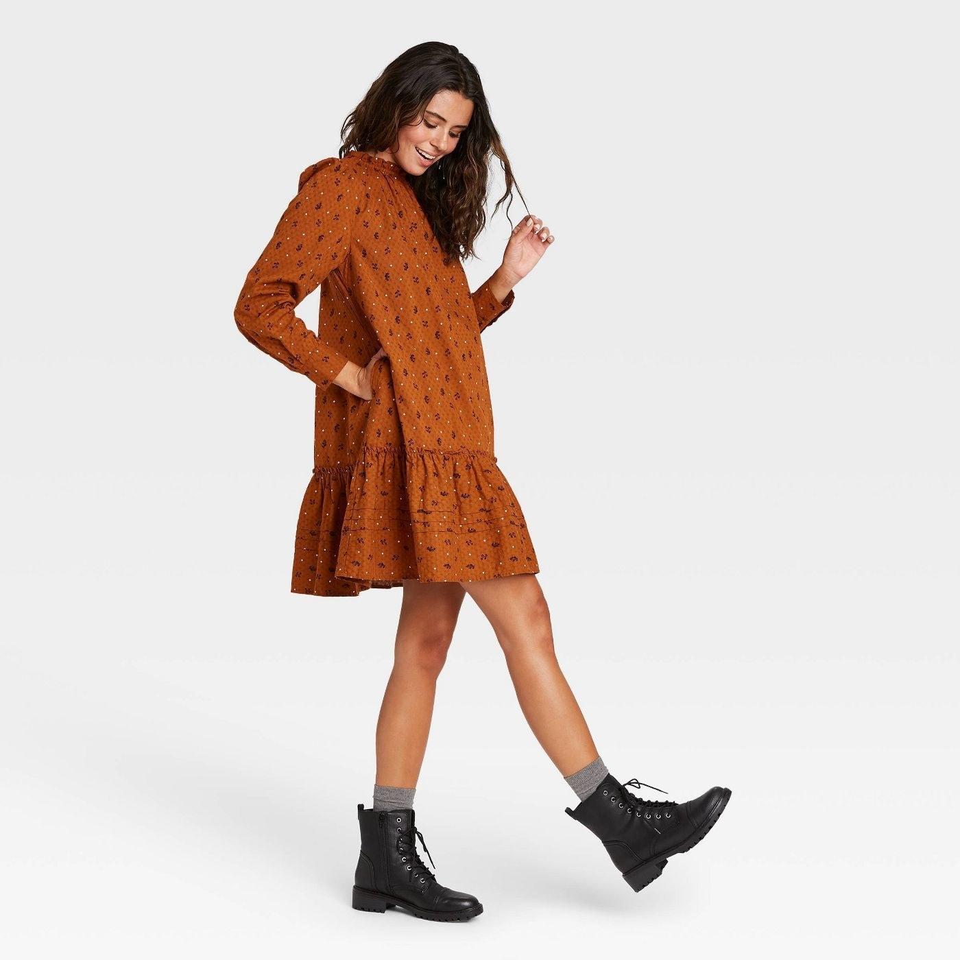 Model wearing burnt orange dress with ruffle hem, stops at the knee