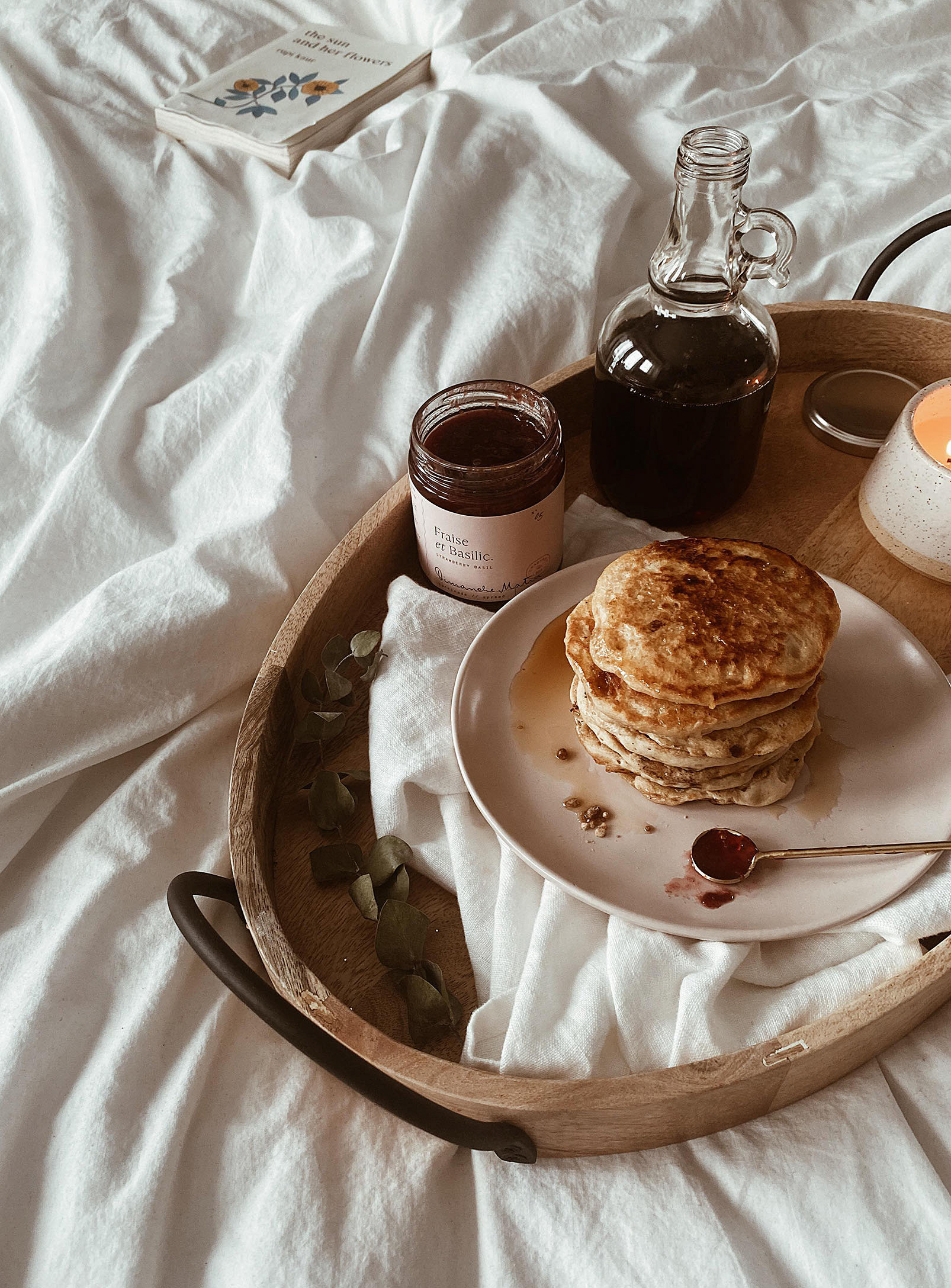 A wooden tray with a plate of pancakes and a jar of jam