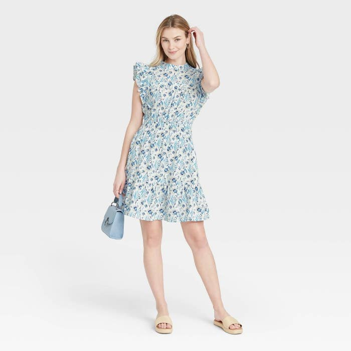 Model wearing white dress with blue floral pattern, stops above the knee