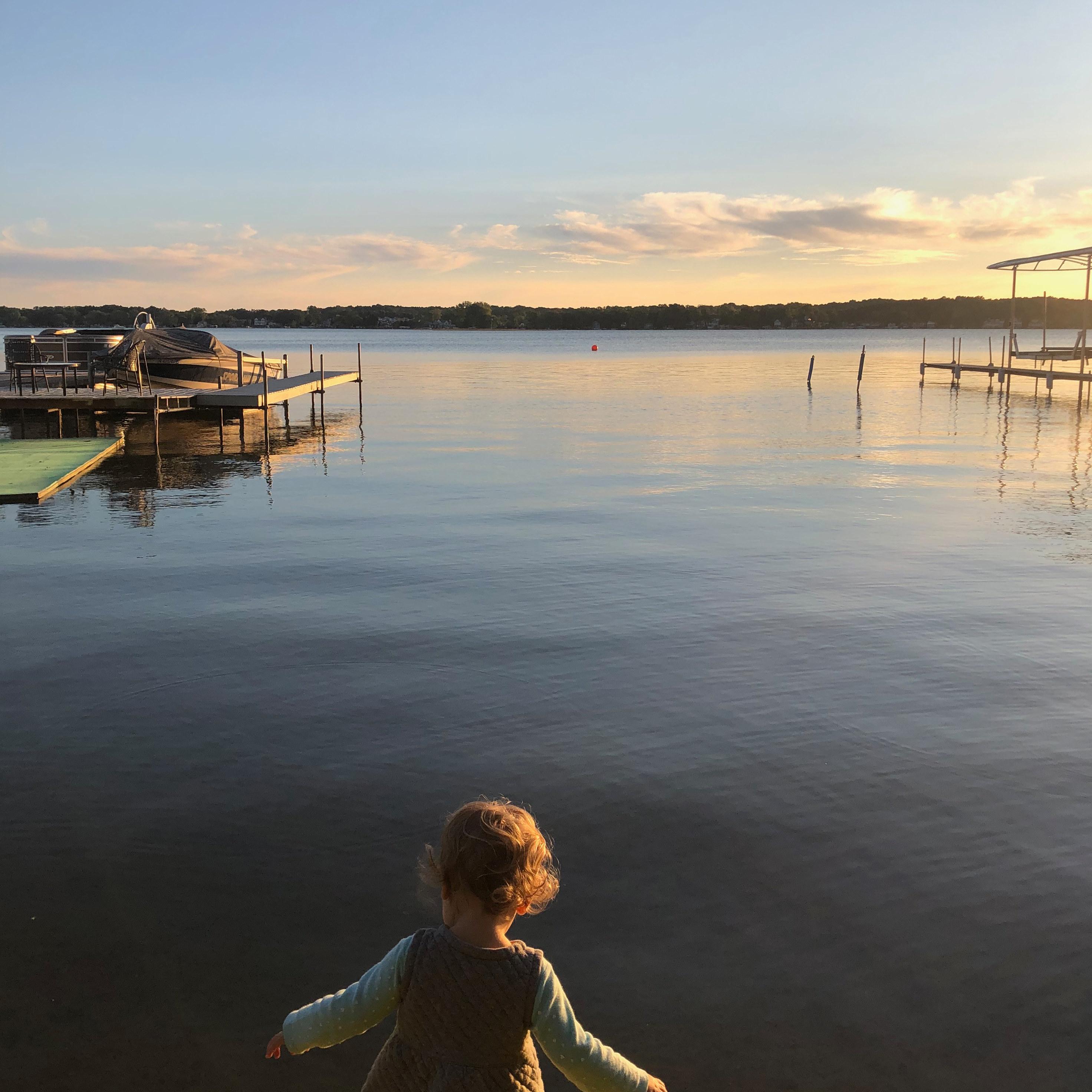 A toddler at the edge of a lake at sunset