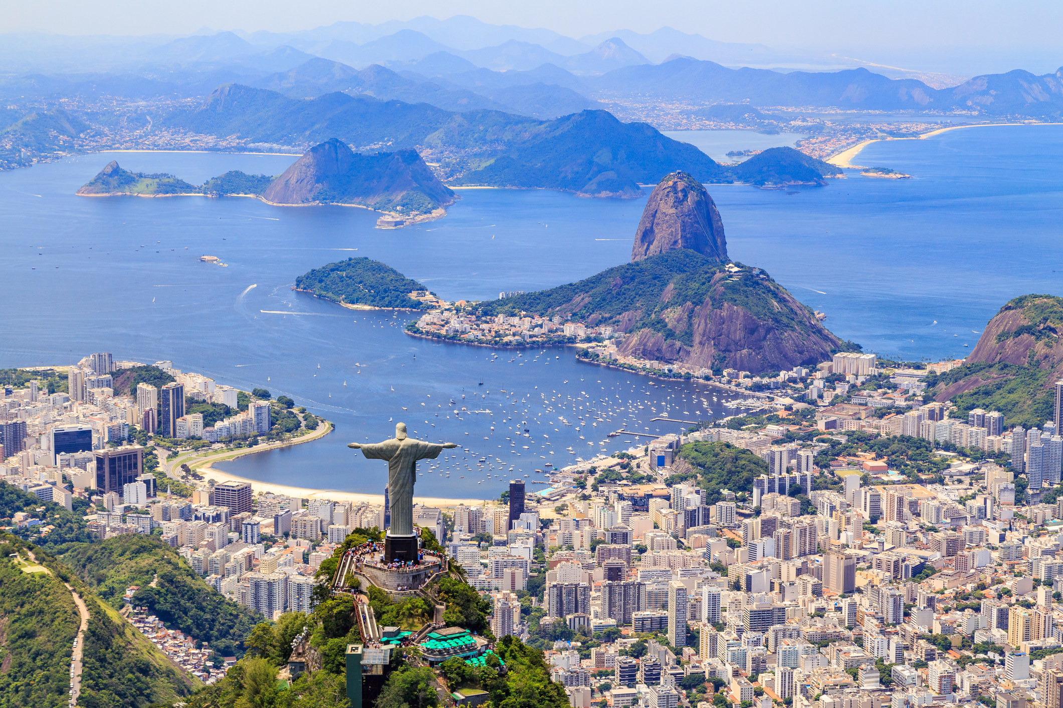 Scene from Rio de Janeiro and shoreline with statue of Christ the Redeemer in the foreground and mountains in the distance