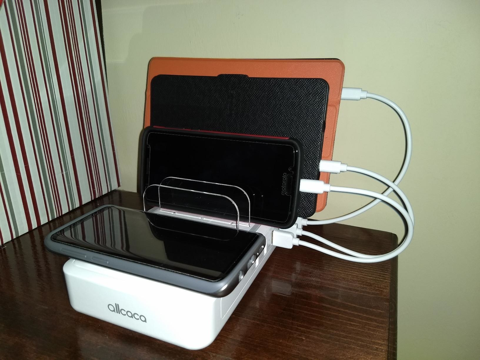 The charger, with a phone on the wireless charging pad, and a phone and two tablets in the charging ports