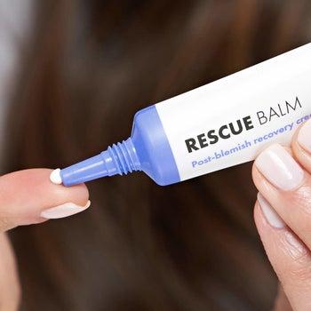Model applying Rescue Balm on finger