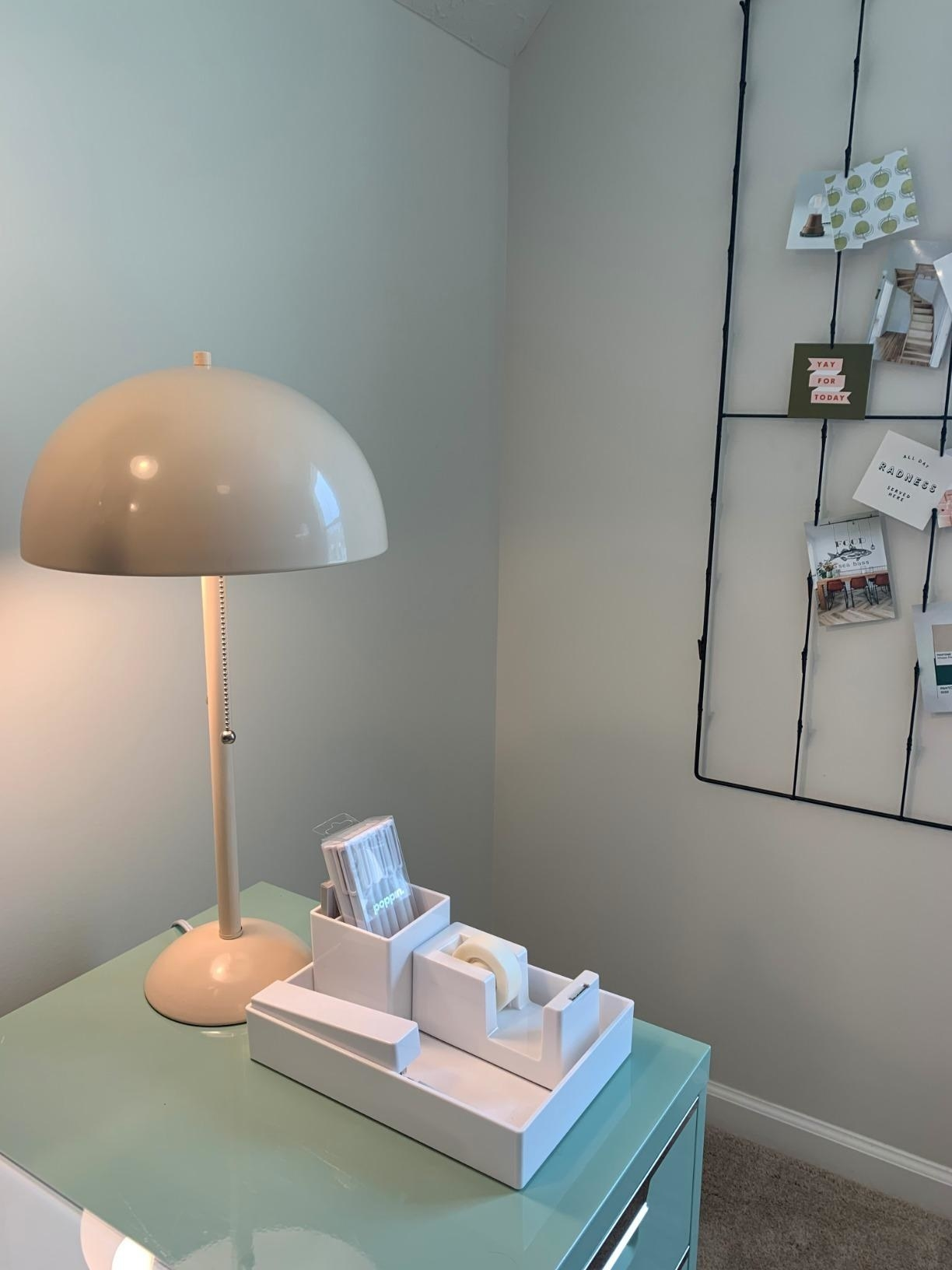 The lamp, which has a round base, thin column, and a rounded dome top, on a reviewer's desk