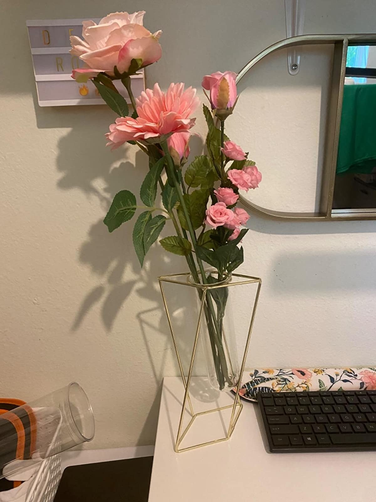 The vase, which has an open geometric wire frame, and a glass bulb to hold flowers and water