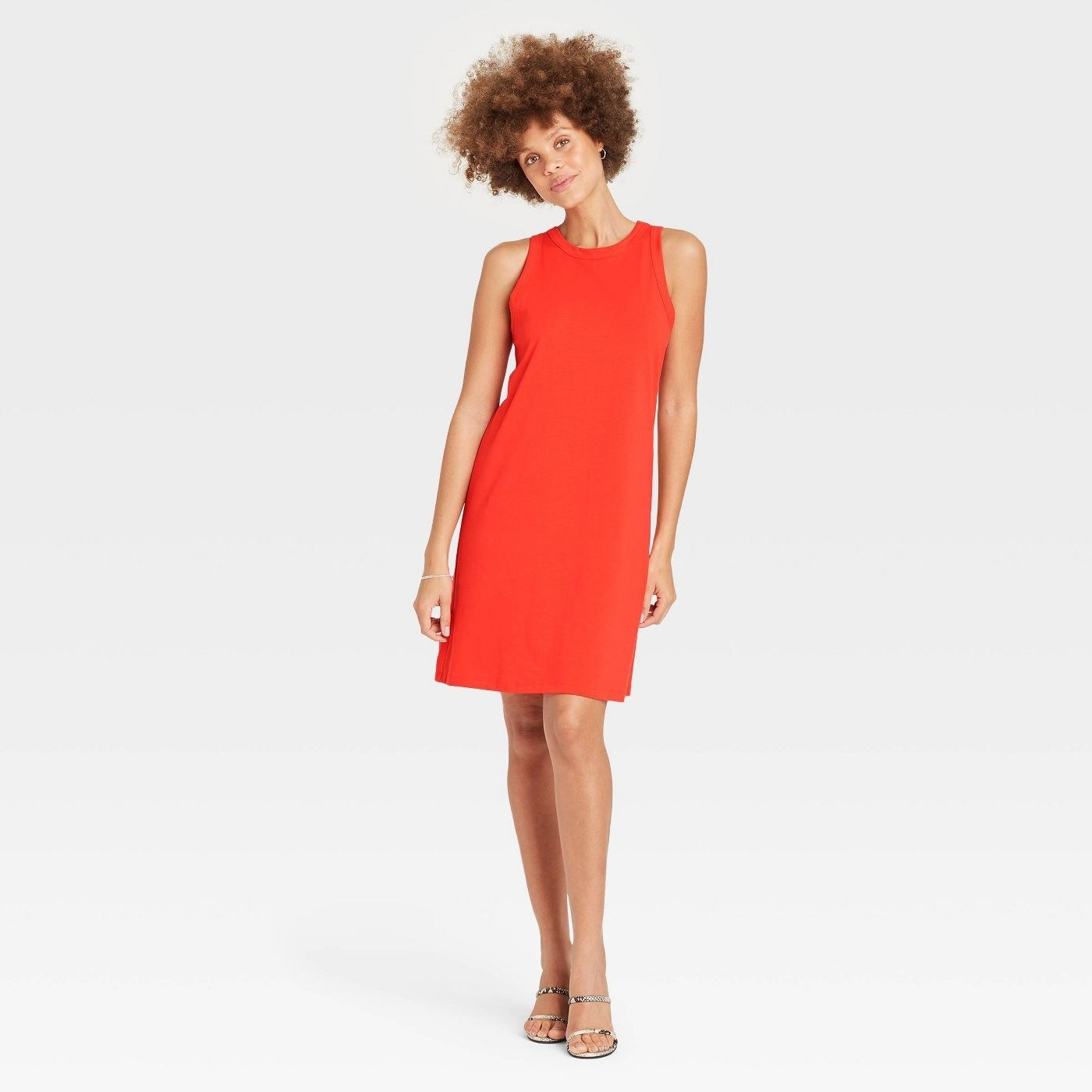 Model wearing orange dress, stops at the knee