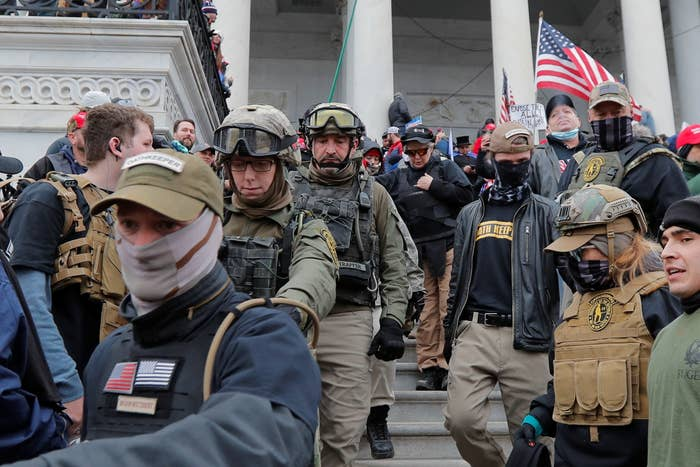 Men wearing camouflage military-style gear and outfits crowd a staircase