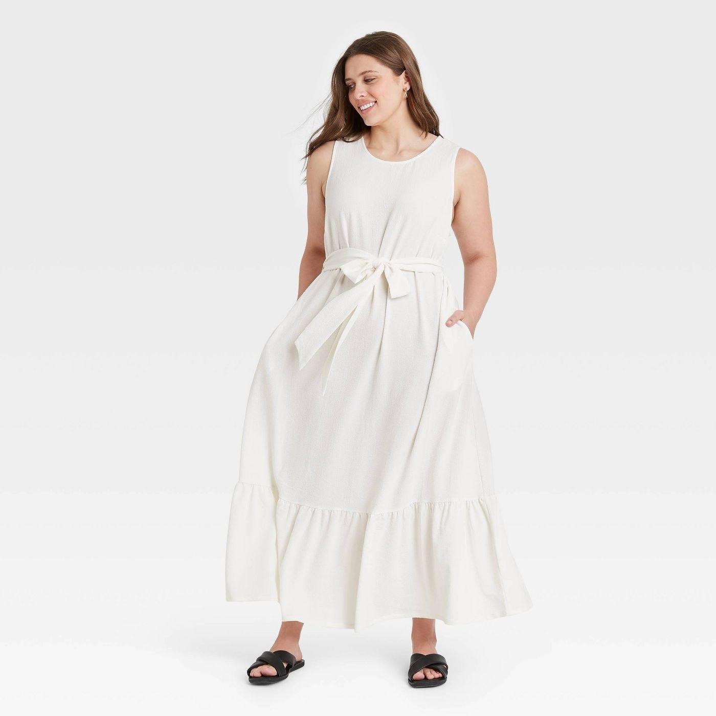 Model wearing white maxi dress with ruffle hem