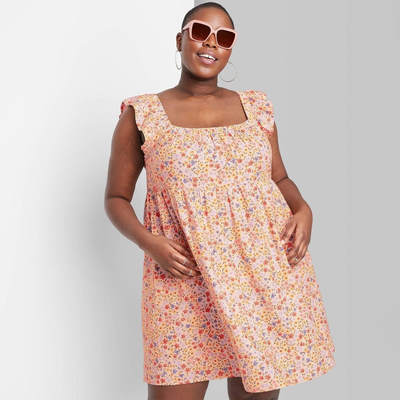 Model wearing orange mini dress with floral print