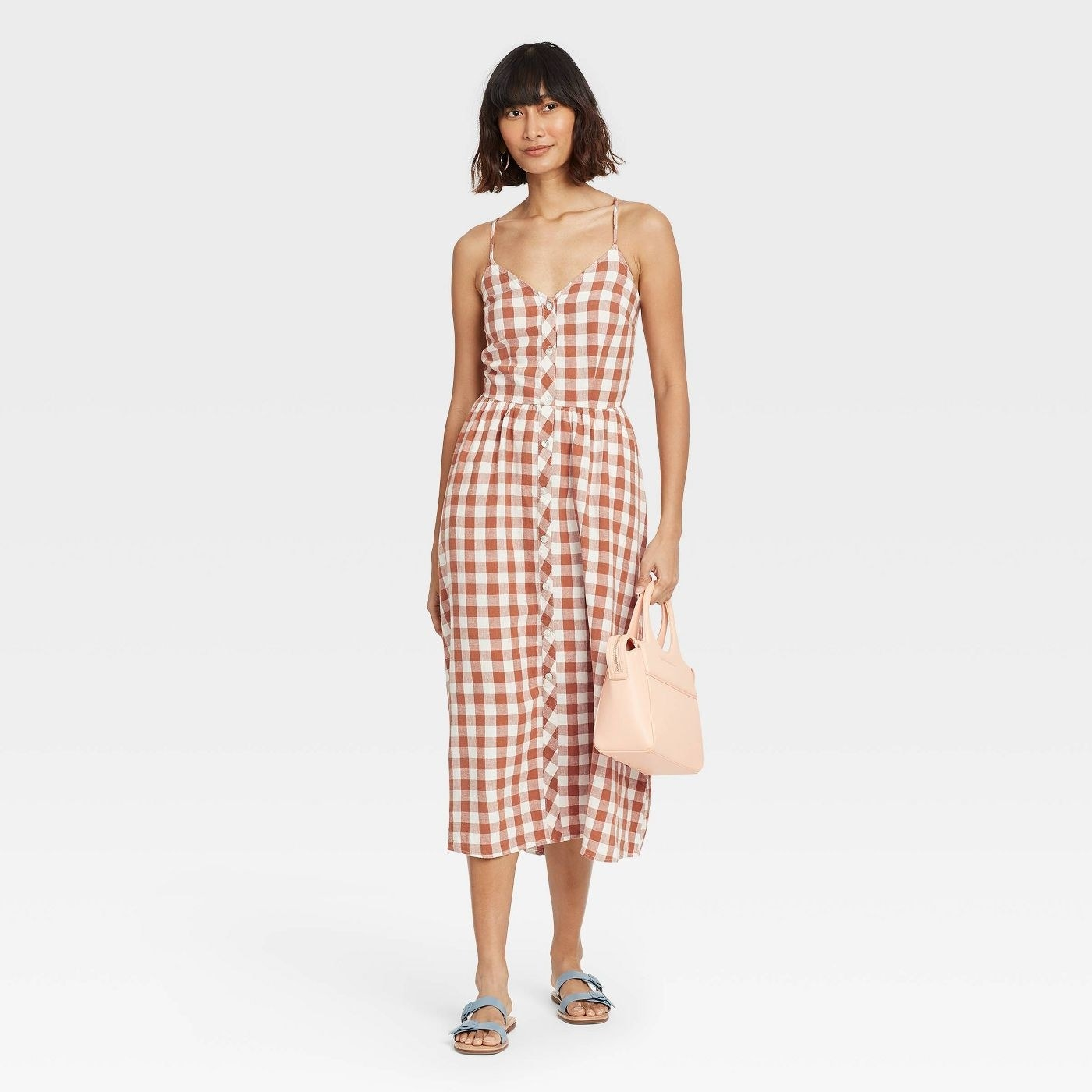 Model wearing midi dress with burnt orange and white checkers
