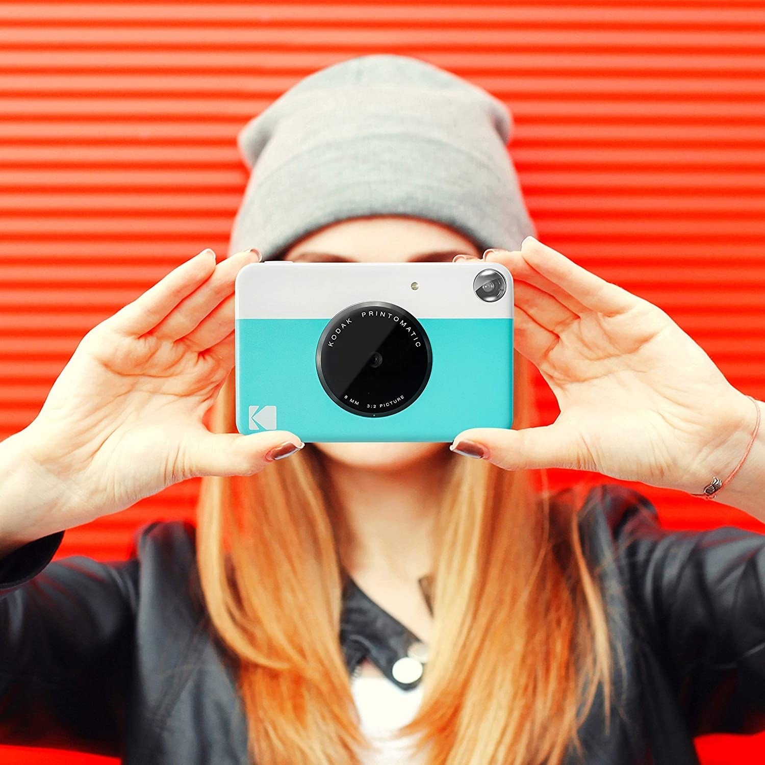 A person holding the print camera.