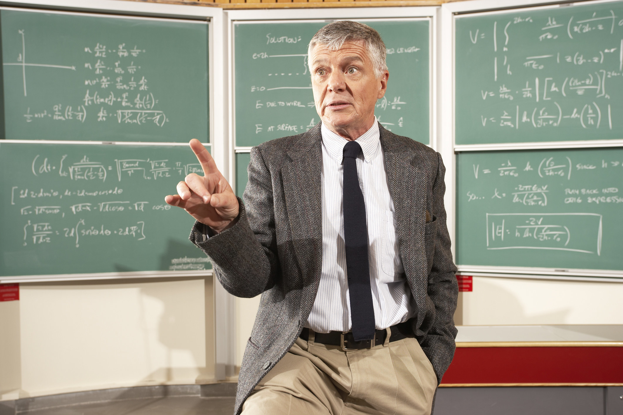 A professor standing in front of a classroom chalkboard