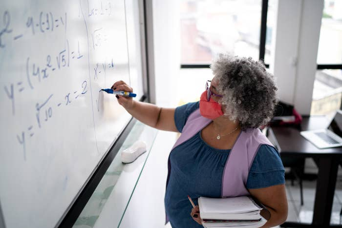 A professor wearing a face mask and writing math equations on a board