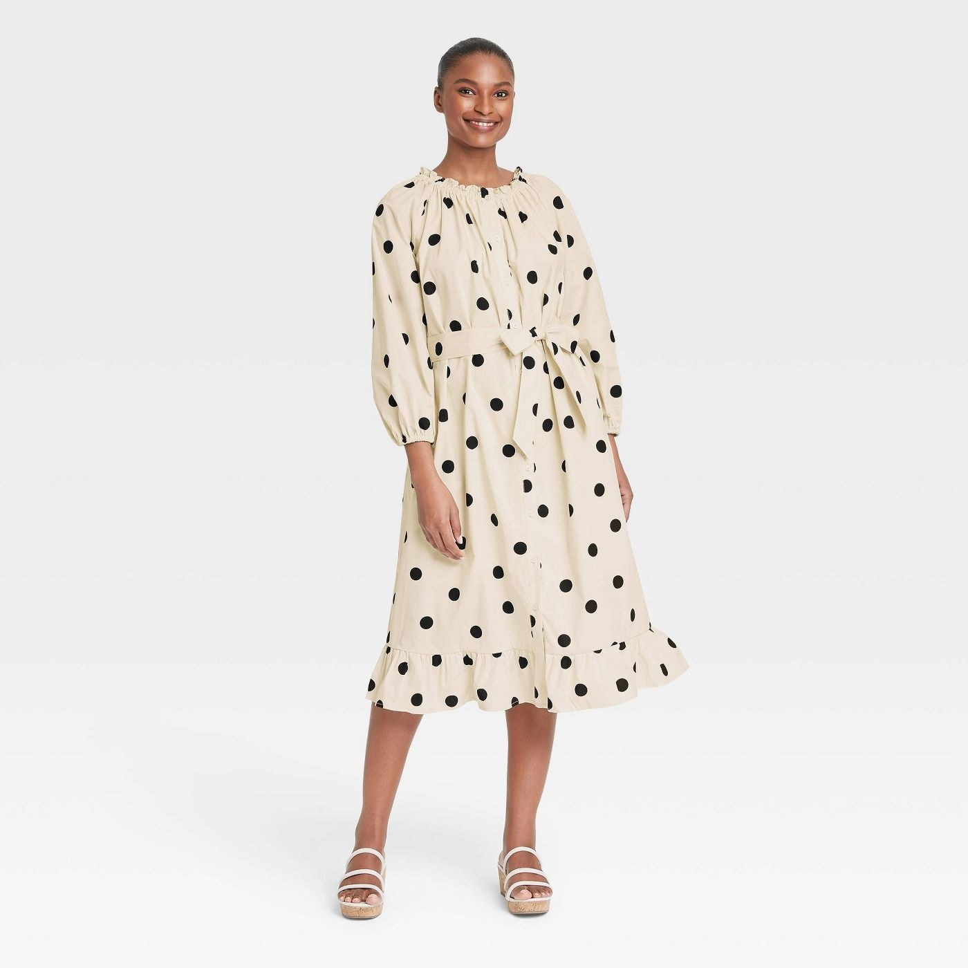 Model wearing off-white dress with black dots, goes past the knee