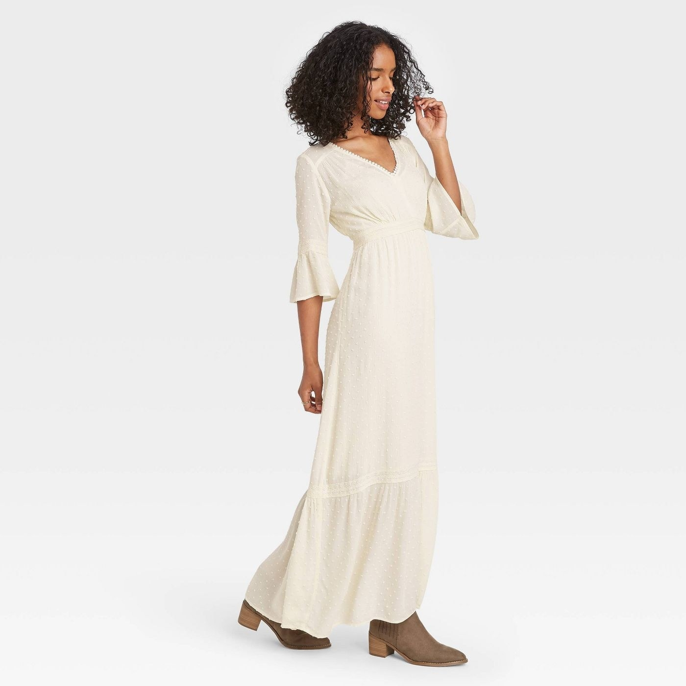Model wearing off off white maxi dress, goes past the ankle