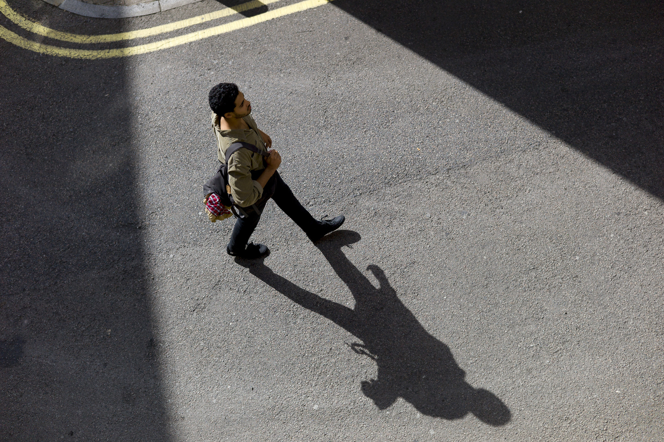 A man walking across the street and his shadow on the pavement