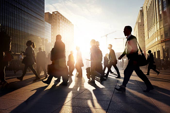 Businesspeople with briefcases and purses walking