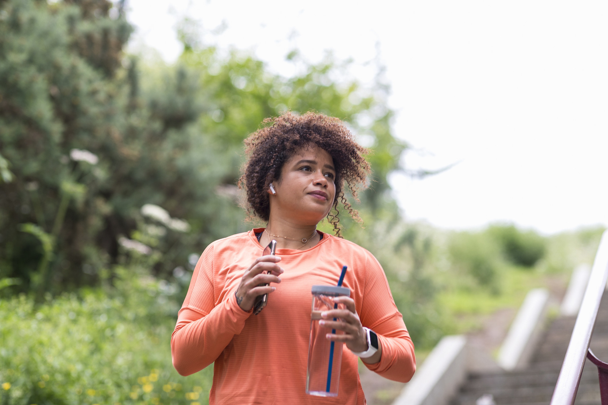 A woman holding a water bottle and her phone as she walks outdoors