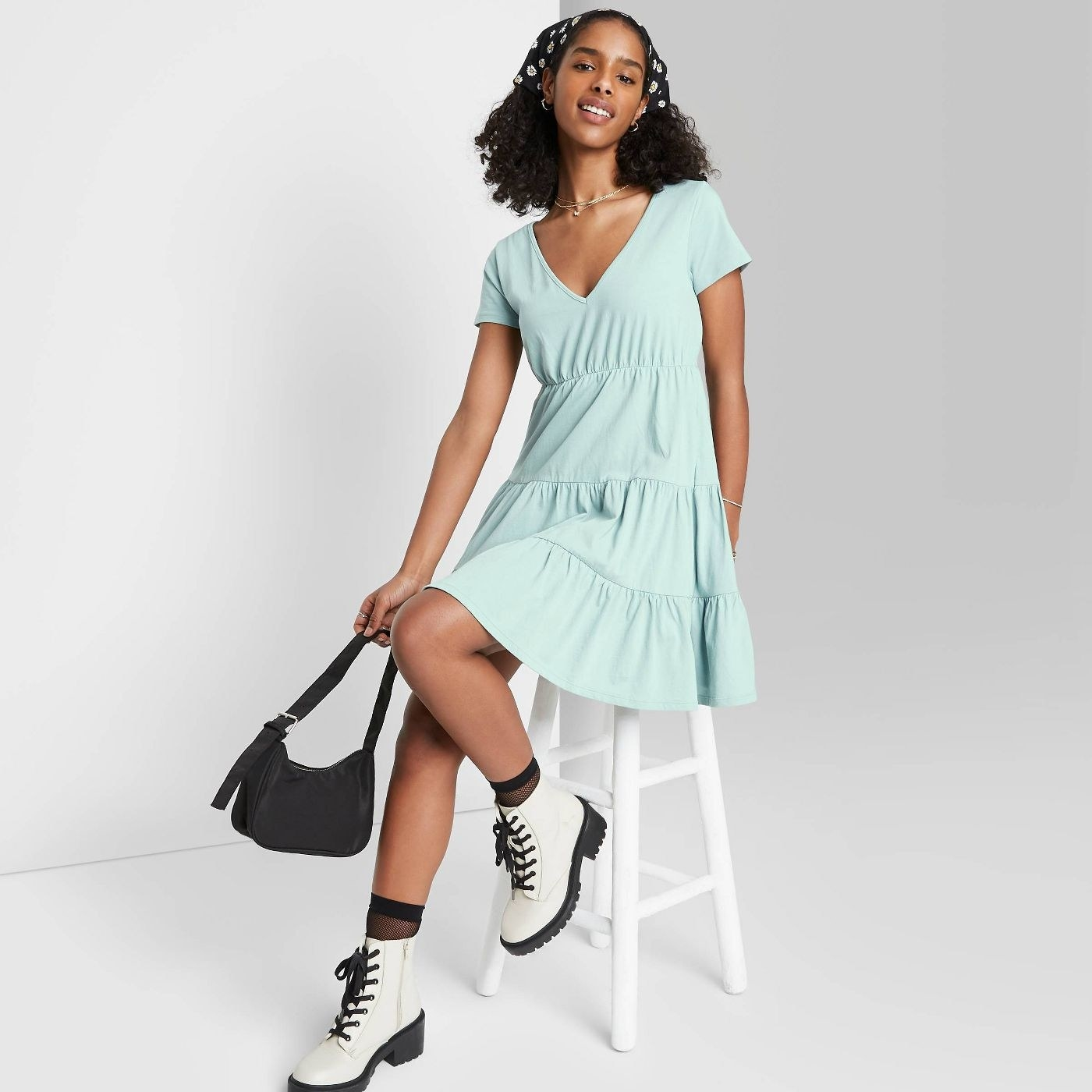 Model wearing light blue v-neck dress with tiered silhouette