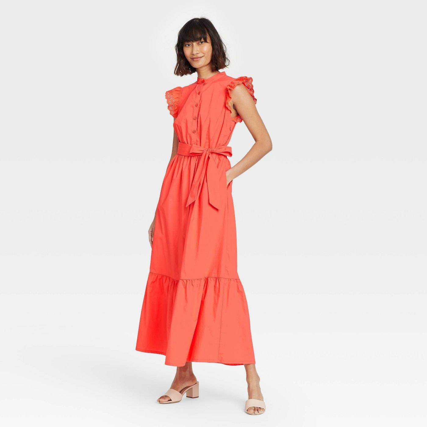 Model wearing short sleeve coral dress with a button down bodice