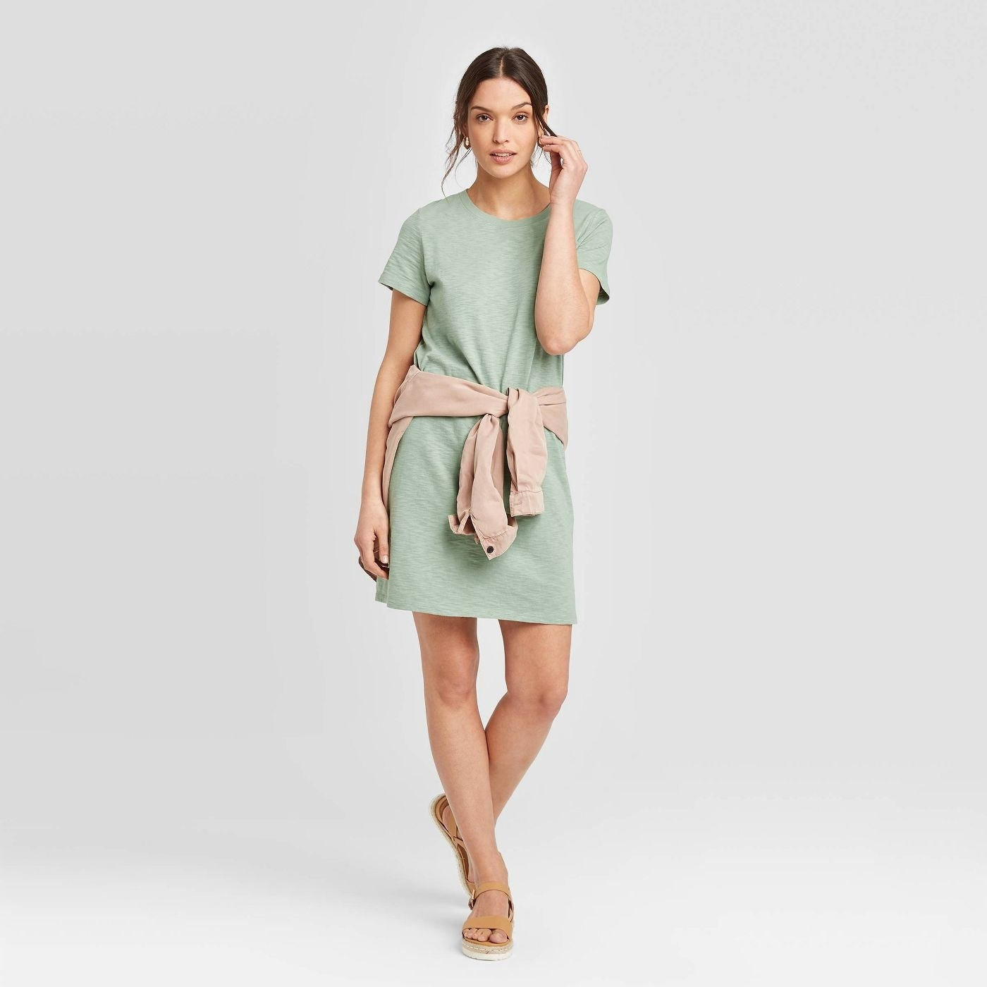 Model wearing green dress, stops above the ankle