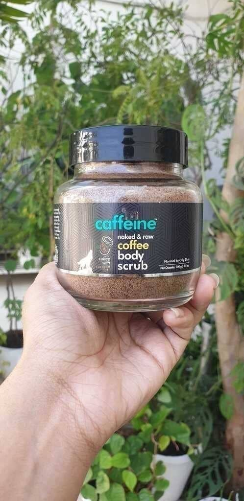 A hand holding the jar of the coffee body scrub.