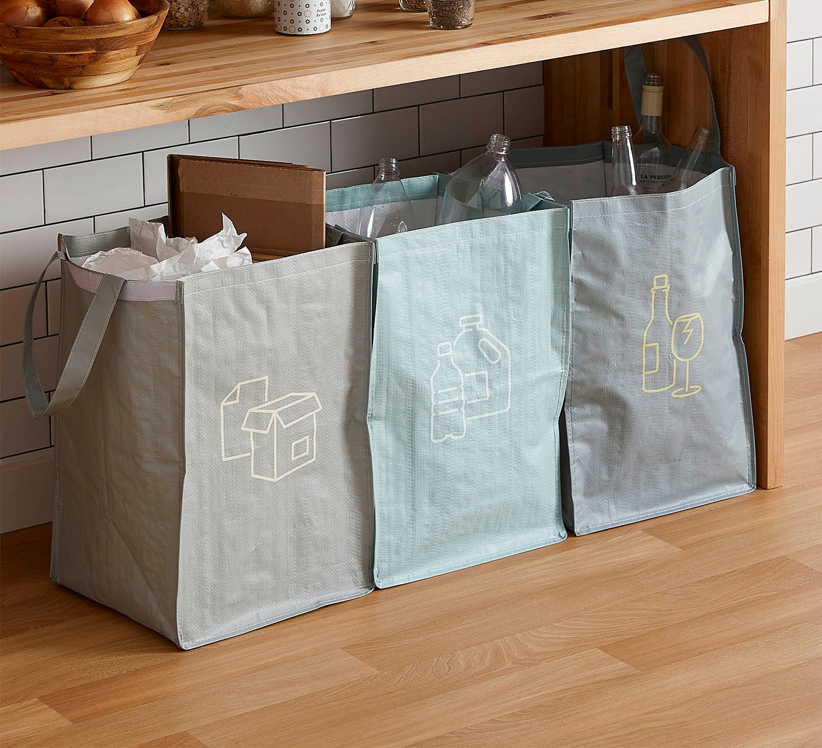 Three large plastic bags with different types of recycled materials in each