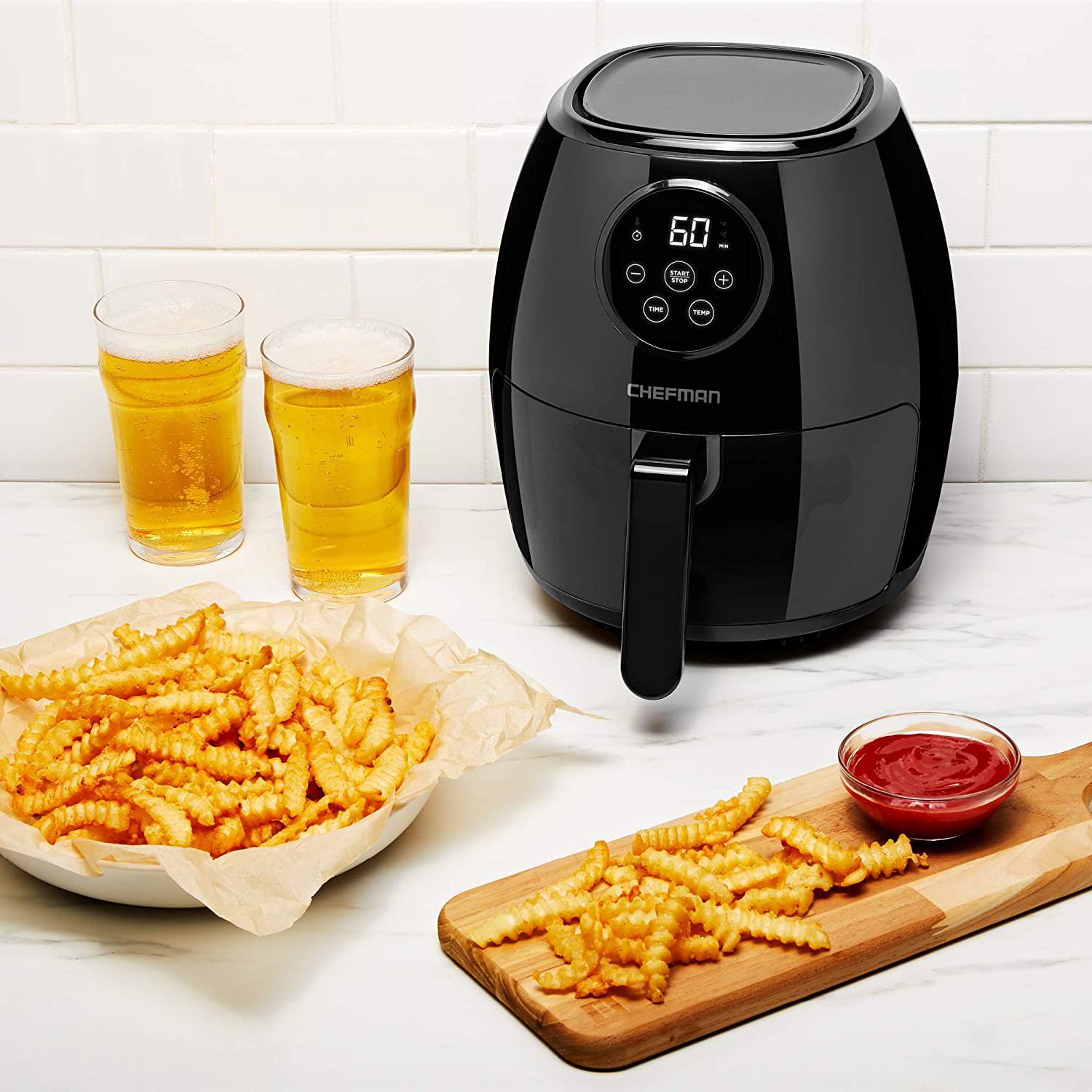 An airfryer appliance next to a plate of curly fries and two mugs of beer
