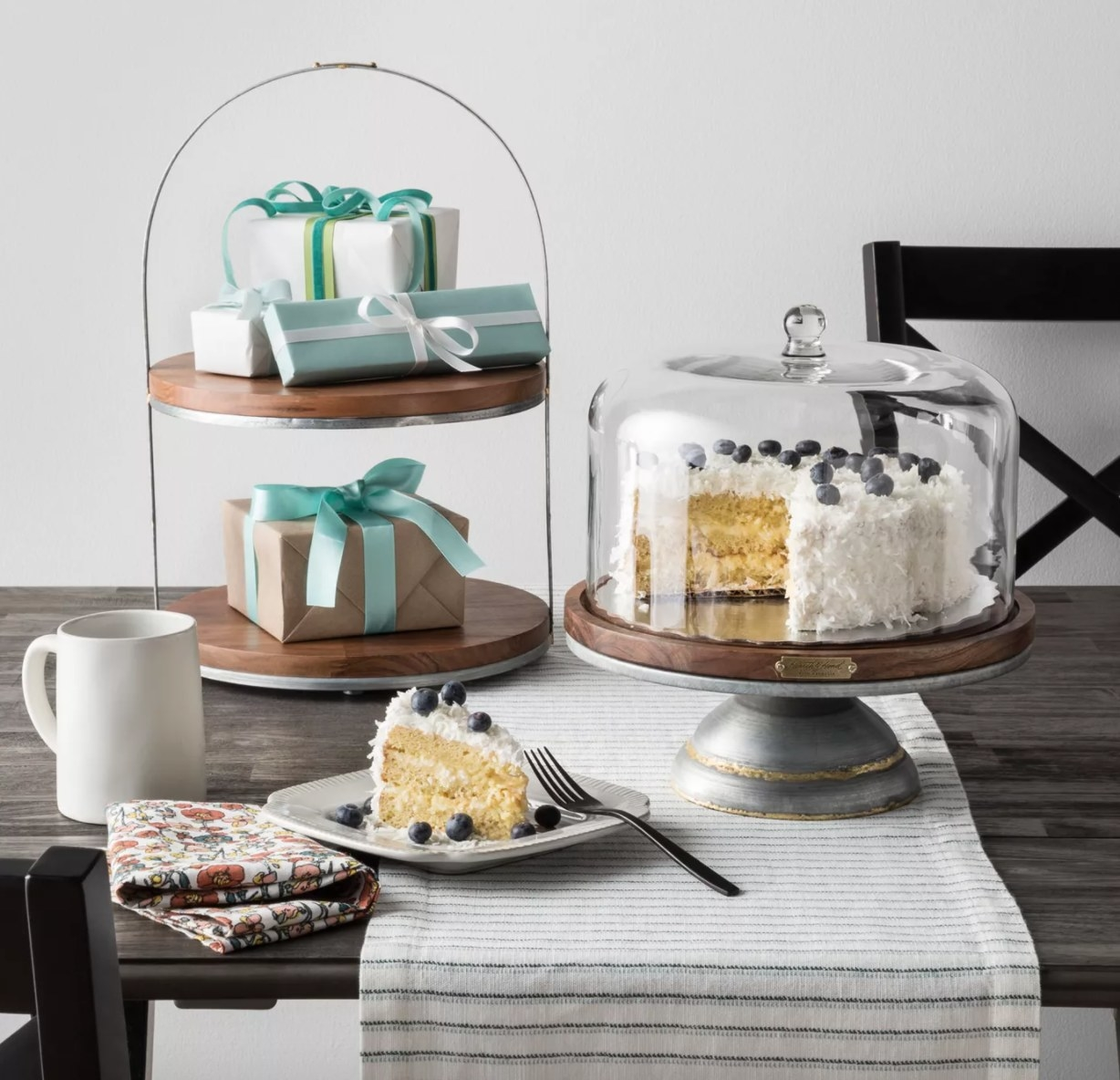 A two tiered dessert stand with wooden surface and metal frame
