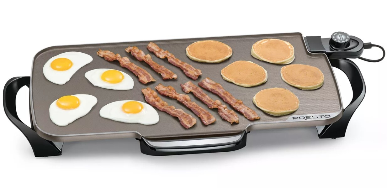 An electric griddle cooking eggs, bacon, and pancakes